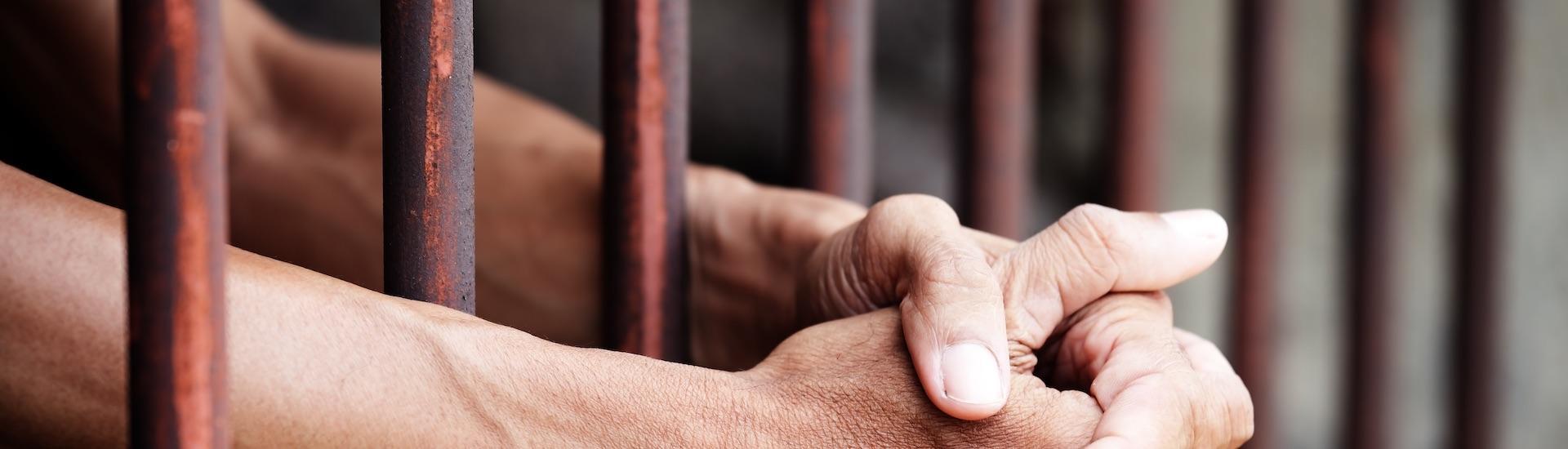 Hands In Prison Bars